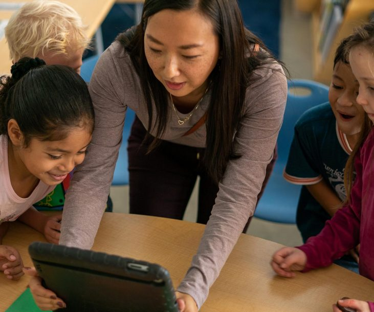 A teacher shows something to her young students on an iPad.